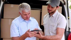Conductor de la entrega que usa la tableta para tomar a clientes la firma metrajes