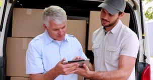 Conductor de la entrega que usa la tableta para tomar a clientes la firma almacen de video