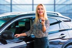 Conductor de la mujer de negocios que lleva a cabo llaves autos delante del coche Foto de archivo libre de regalías