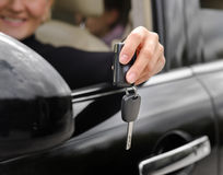 Conductor de la mujer que lleva a cabo hacia fuera sus llaves del coche Imagen de archivo libre de regalías
