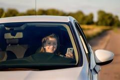 Conductor de la mujer que sonríe como ella lee SMS Fotografía de archivo libre de regalías