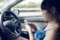 Conductor de la mujer que usa un teléfono elegante Imágenes de archivo libres de regalías