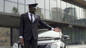 Conductor de lujo del servicio del taxi que acoge con satisfacción al cliente muy importante cerca del coche costoso almacen de metraje de vídeo