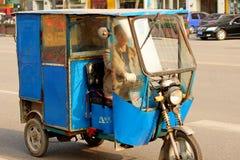 Conductor de Tuk Tuk (taxi) en China Fotos de archivo