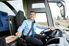 Conductor del autobús que toma el boleto o la tarjeta del pasajero Imágenes de archivo libres de regalías