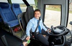 Conductor del autobús que toma el boleto o la tarjeta del pasajero Foto de archivo