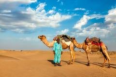 Conductor del camello de Cameleer con los camellos en dunas de Thar Imágenes de archivo libres de regalías