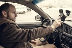 Conductor del hombre joven que usa smartphone en coche foto de archivo