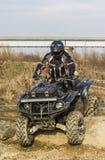 Conductor del patio de ATV en la acción Superar un obstáculo del tronco Imagen de archivo