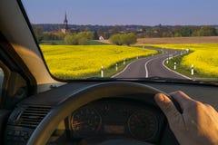 Conductor detrás de la rueda que conduce abajo de una carretera nacional Imagen de archivo