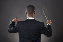 Conductor Directing With His Baton. Young African Conductor Directing With His Baton Against Black Background Royalty Free Stock Photos
