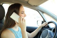 Conductor distraído que invita al teléfono que conduce un coche imagen de archivo libre de regalías