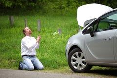 Conductor divertido que ruega un coche quebrado Foto de archivo libre de regalías