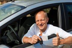 Conductor emocionado que lleva a cabo las llaves de su nuevo coche Foto de archivo