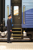 Conductor beside entry in train Stock Image