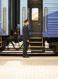Conductor beside entry in train. Conductor to stand beside entry in train Royalty Free Stock Images