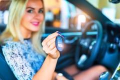 Conductor feliz de la mujer que lleva a cabo llaves autos en su coche Foto de archivo libre de regalías