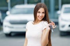 Conductor feliz de la mujer que muestra llave del coche Imágenes de archivo libres de regalías