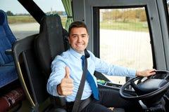 Conductor feliz que conduce el autobús y los pulgares que nievan para arriba Imágenes de archivo libres de regalías