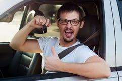 Conductor feliz que lleva a cabo llaves del coche Imagen de archivo