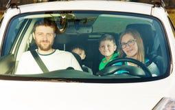 Conductor femenino feliz que se sienta en coche con su familia fotos de archivo