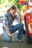 Conductor femenino frustrado With Tyre Iron que intenta a la rueda de cambio imagen de archivo