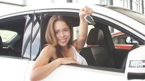 Conductor femenino joven cauc?sico feliz que se sienta en las llaves blancas del coche de las demostraciones de coche en la sala  metrajes