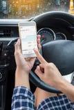 Conductor femenino joven que usa smartphone de la pantalla táctil en un coche Foto de archivo