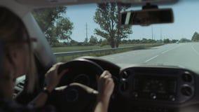 Conductor femenino que conduce el coche en autopista sin peaje en viaje por carretera metrajes