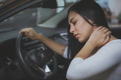 Conductor femenino que frota su cuello de dolor después de long drive imagenes de archivo