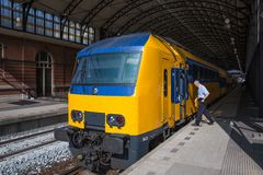 Conductor getting in a train ready to start in The Hague, the Netherlands Royalty Free Stock Image