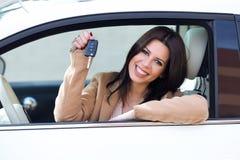 Conductor hermoso de la mujer joven que lleva a cabo llaves autos en su nuevo coche fotografía de archivo