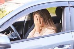 Conductor infeliz de la muchacha Dado una sacudida eléctrica y asustado Accidente de tráfico imagenes de archivo