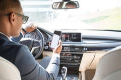 Conductor joven del hombre de negocios en las gafas de sol que se sientan dentro de la conducción de automóviles usando el app de imágenes de archivo libres de regalías