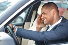 Conductor joven del hombre de negocios que se sienta dentro de la conducción de automóviles tocando la vista lateral del dolor pr foto de archivo