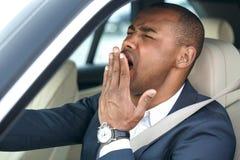 Conductor joven del hombre de negocios que se sienta dentro de la opinión cansada de bostezo de la conducción de automóviles en p imagenes de archivo