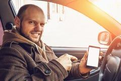 Conductor joven en su coche que sostiene smartphone o el teléfono con la pantalla blanca vacía como mofa ascendente o en blanco p imagen de archivo