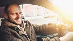 Conductor joven feliz hermoso que sonríe mientras que conduce su coche en efecto luminoso del sol imagenes de archivo