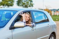 Conductor joven hermoso que mira fuera del coche que lleva a cabo llave Fotos de archivo libres de regalías