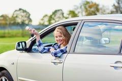 Conductor joven hermoso que mira fuera del coche que lleva a cabo llave Imagen de archivo