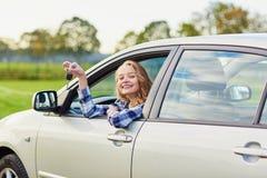 Conductor joven hermoso que mira fuera del coche que lleva a cabo llave Imagenes de archivo