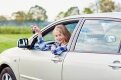 Conductor joven que mira fuera de la ventanilla del coche que lleva a cabo una llave Imagen de archivo