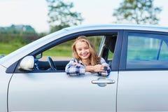 Conductor joven que mira fuera de la ventanilla del coche que lleva a cabo una llave Fotos de archivo libres de regalías