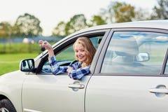 Conductor joven que mira fuera de la ventanilla del coche que lleva a cabo una llave Fotografía de archivo libre de regalías