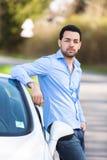 Conductor latinoamericano asentado en el lado de su nuevo coche Fotografía de archivo