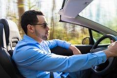 Conductor latinoamericano negro que conduce su nuevo coche Fotos de archivo libres de regalías