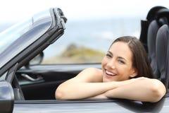 Conductor loking en usted en un coche convertible el vacaciones Fotografía de archivo
