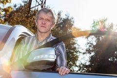 Conductor maduro que coloca el coche cercano con la puerta abierta y la luz del sol en fondo Imagenes de archivo