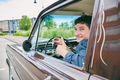 Conductor masculino feliz que muestra llaves en ventanilla del coche abierta Fotos de archivo libres de regalías