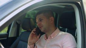 Conductor masculino hermoso que invita al teléfono elegante en coche metrajes
